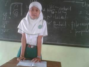 Seorang siswi sedang presentasi hasil belajar
